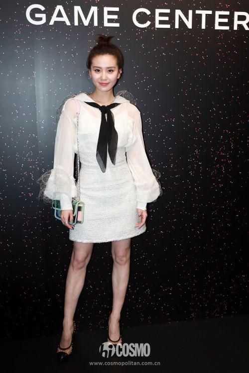 Chanel 2018春夏系列白色蕾丝拼接灯笼袖衬衫,下穿Chanel 2018春夏系列白色毛呢高腰短裙,肩背Chanel拼色PVC链条包,脚踩拼接透视珍珠高跟鞋。